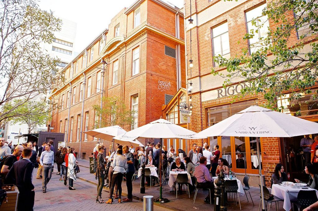People milling about drinking wine outside a restaurant in an activated laneway