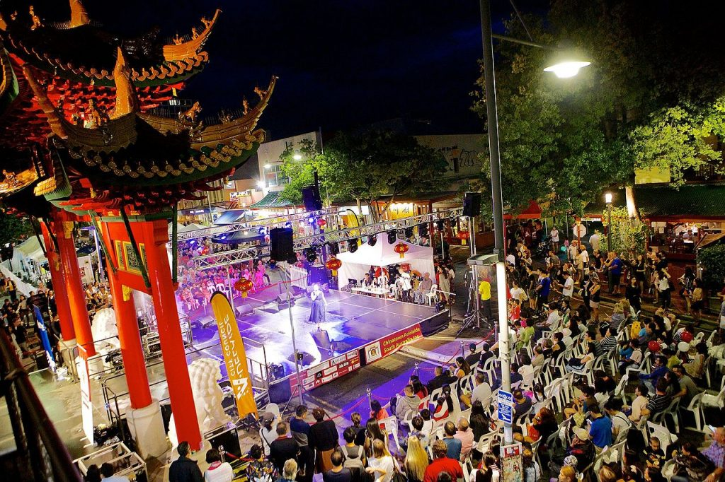 A crowd of people watching a performer on stage at night in chinatown